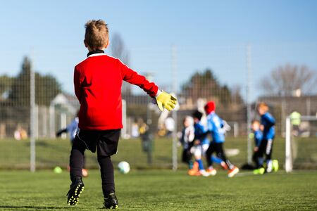 Young goal keeper and his youth team during a kids soccer match outdoors on green soccer pitch.