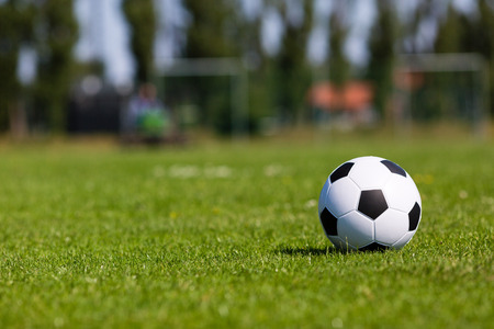 green field: Black and white soccer ball on green soccer pitch. Stock Photo