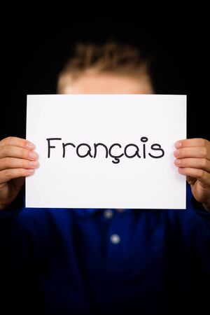 francais: Studio shot of child holding a sign with French word Francais - French