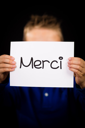 merci: Studio shot of child holding a sign with French word Merci - Thank You Stock Photo