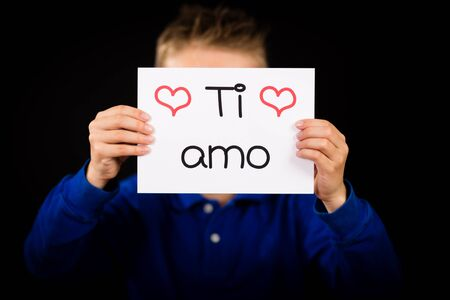 te amo: Tiro del estudio de la celebraci�n de un cartel con las palabras italianas Ti Amo ni�o - Te Quiero