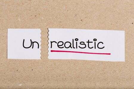 unrealistic: Two pieces of white paper with the word unrealistic turned into realistic