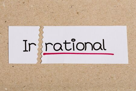 rational: Two pieces of white paper with the word irrational turned into rational Stock Photo