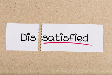 Two pieces of white paper with the word dissatisfied turned into satisfied Stock Photo