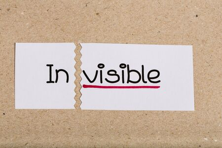 visible: Two pieces of white paper with the word invisible turned into visible