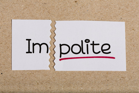 Two pieces of white paper with the word impolite turned into polite Stock Photo