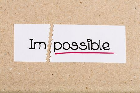 two visions: Two pieces of white paper with the word impossible turned into possible Stock Photo