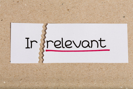 irrelevant: Two pieces of white paper with the word irrelvant turned into relevant