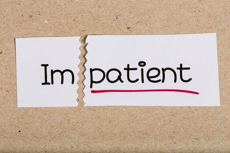 underscore: Two pieces of white paper with the word impatient turned into patient