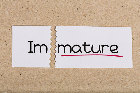 Two pieces of white paper with the word immature turned into mature