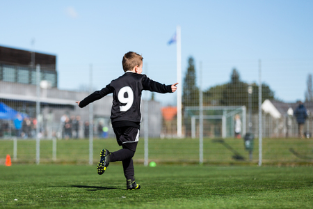 soccer sport: Young boy and his youth team during a kids soccer match outdoors on green soccer pitch. Stock Photo