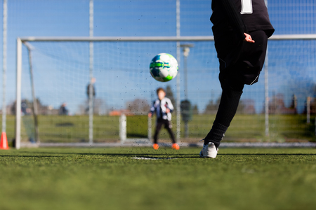 goal kick: Close-up of young soccer player taking a penalty kick against a young blurred boy acting as goalie in the goal.