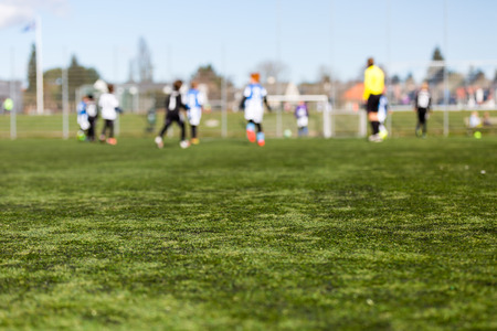 Blur of young kids playing a youth soccer match outdoors on an green soccer pitch. Stockfoto