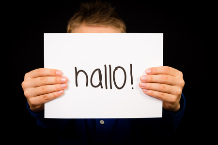 hallo: Studio shot of child holding a sign with German word Hallo - Hello in English