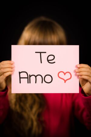 Te: Studio shot of child holding a sign with Spanish words Te Amo - I Love You