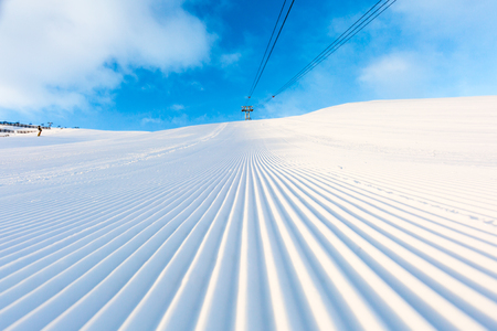 groomed: Newly groomed snow on ski slope at ski resort on a sunny winter day. Stock Photo