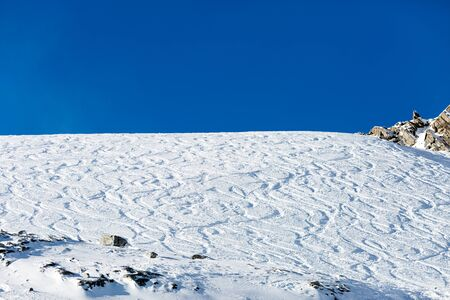 off piste: Off piste ski tracks on powder snow on a sunny winter day with blue sky. Stock Photo