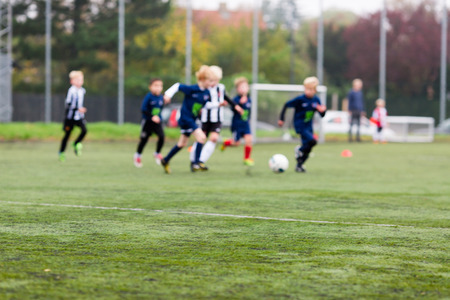junior soccer: Young kids during a boys soccer match on green soccer pitch. Stock Photo