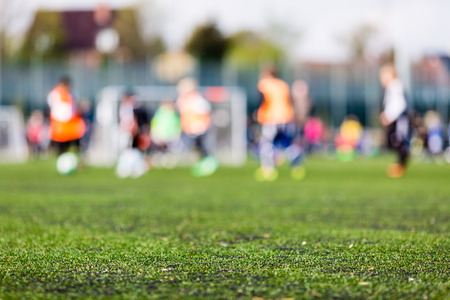 Shallow depth of field shot of young boys playing a kids soccer match on green turf. Stock Photo