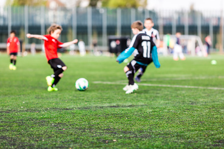 jugando futbol: Poca profundidad de campo de tiro de chicos jóvenes que juegan un partido de fútbol de los cabritos en césped verde. Foto de archivo