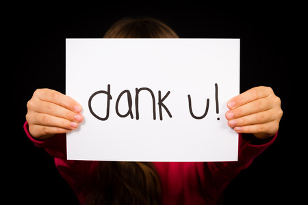 dank: Studio shot of child holding a sign with Dutch words Dank U - Thank You Stock Photo