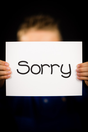 excuse: Studio shot of child holding a Sorry sign made of white paper with handwriting. Stock Photo