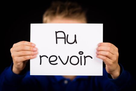 au: Studio shot of child holding a sign with French word Au Revoir - Goodbye Stock Photo