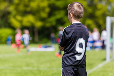 substitute: Young boy watching his team mates play a kids soccer match on soccer field with green grass.