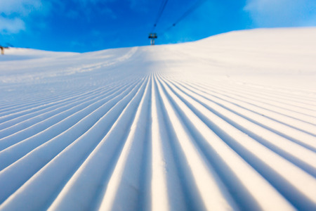 Newly groomed snow on ski slope at ski resort on a sunny winter day. Stockfoto