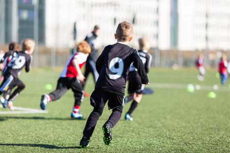 futbol soccer: Los niños pequeños que juegan un partido de entrenamiento de fútbol al aire libre en un campo de fútbol artificial.