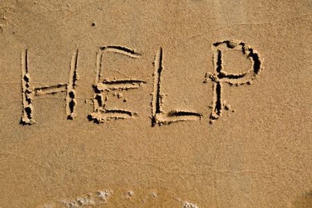 cry for help: Casual writing in the wet sand on a sunny day. Stock Photo