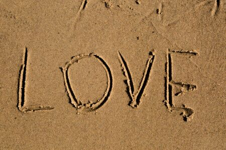 sand writing: Casual writing in the wet sand on a sunny day. Stock Photo