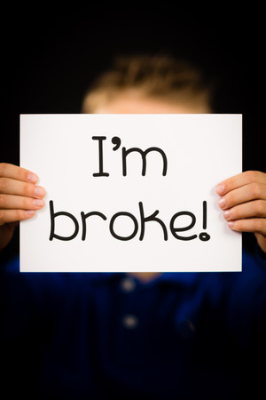 i kids: Studio shot of child holding an I am Broke sign made of white paper with handwriting.