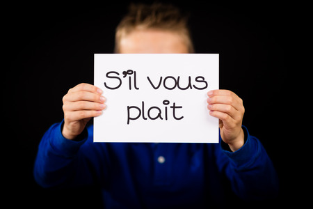 il: Studio shot of child holding a sign with French words S il Vous Plait - Please