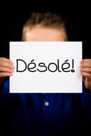 excuse: Studio shot of child holding a sign with French word Desole - Sorry Stock Photo