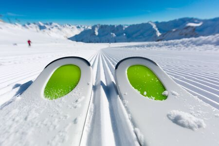 ski track: Pair of ski tips standing on the fresh snow on newly groomed  ski piste at ski resort on a sunny winter day. Stock Photo