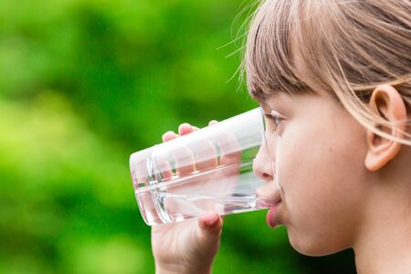 drinking water: Close-up of young scandinavian child drinking fresh and pure tap water from glass with a blurred green background. Stock Photo