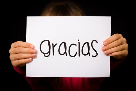 merci: Studio photo d'un enfant tenant un signe avec le mot espagnol Gracias - Merci