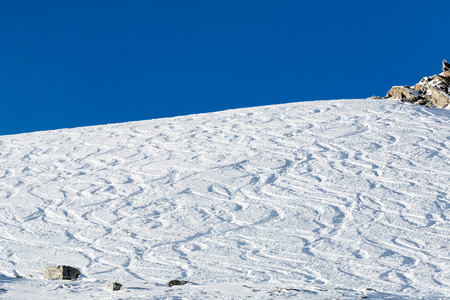 freeride: Off piste ski tracks on powder snow on a sunny winter day with blue sky. Stock Photo