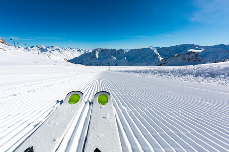 Pair of ski tips standing on the fresh snow on newly groomed  ski piste at ski resort on a sunny winter day. Stock Photo