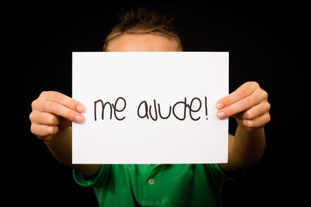 help me: Studio shot of child holding a sign with Portuguese words Me Ajude - Help Me