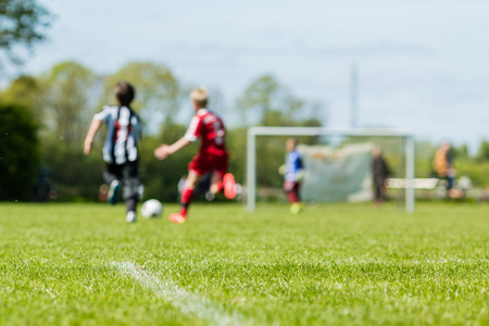 Shallow depth of field shot of young boys playing a kids soccer match on green grass. Stock Photo