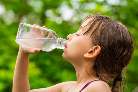 Closeup of young girl drinking fresh cold tap water from transparent plastic drinking bottle while outdoors on a hot summer day.
