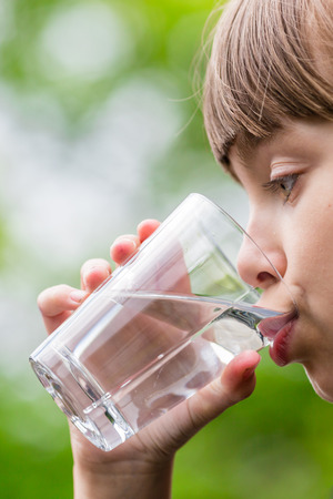 Close-up of young scandinavian child drinking fresh and pure tap water from glass with a blurred green background. Stock Photo