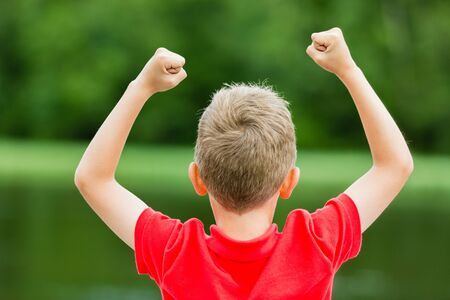 Boy with raised arms and fists in the air celebrating success or victory.