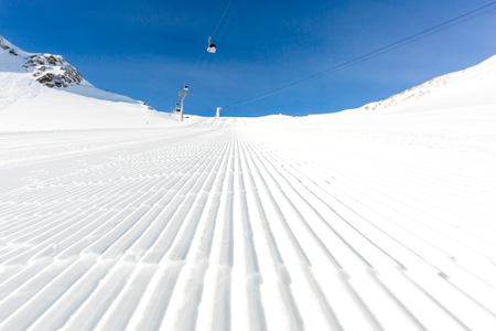 groomed: Fresh snow at recently groomed ski run at ski resort in the Alps on a sunny winter day. Stock Photo