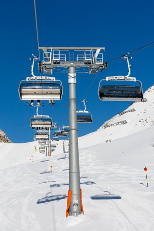 chair on the lift: The ski resort Soelden in the Alps with chair lift and ski slope with descending skiers. Stock Photo