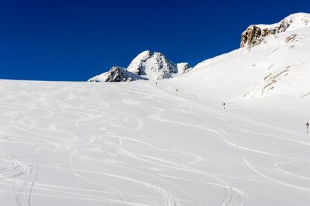piste: Fresh ski tracks on ski slope with new white snow at the ski resort Soelden in the Austrian Alps.
