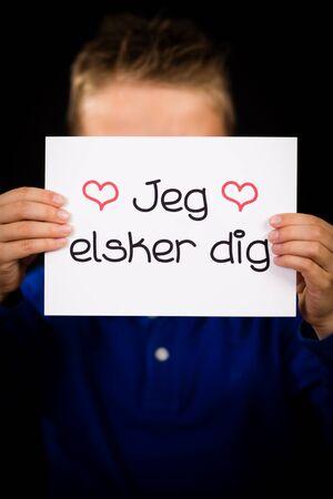 dig: Studio shot of child holding a sign with Danish words Jeg Elsker Dig - I Love You