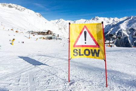 piste: Yellow slow down warning sign placed in the snow on the piste at the ski resort Soelden in Austria.